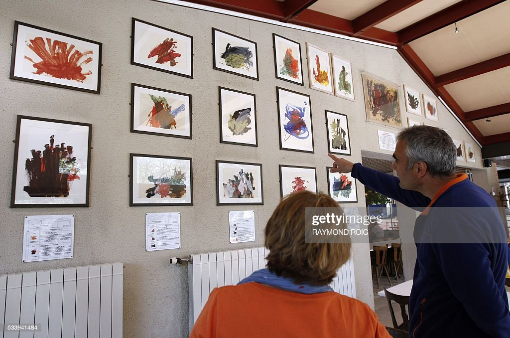 Visitors look at framed painting by chimps displayed in a building in the grounds of the African Reserve (Réserve Africaine ) wildlife park in Sigean, southern France on May 24, 2016. / AFP / RAYMOND