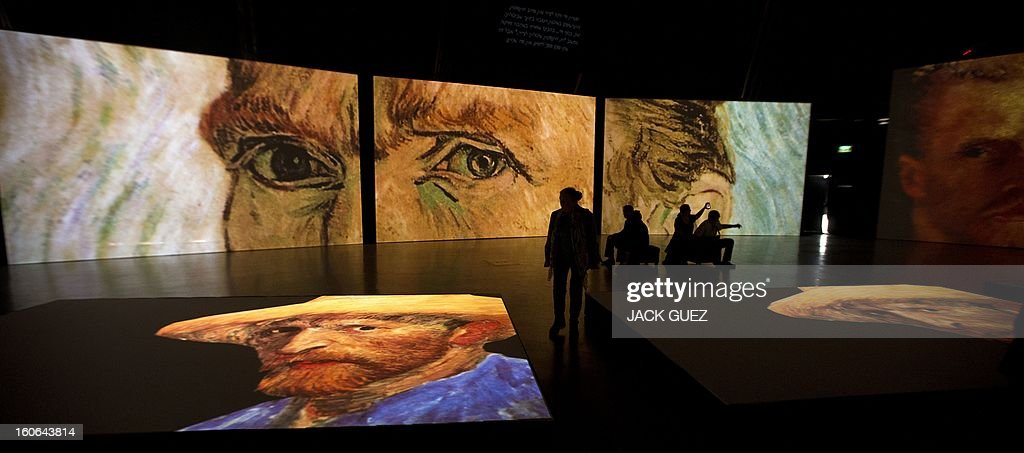 Visitors look at giant screens featuring images of the work of Dutch painter Vincent van Gogh during a traveling multimedia art exhibition entitled 'Van Gogh alive' on February 4, 2013 at the Israel Trade Fairs and Convention Center in Tel Aviv. The interactive installation, featuring thousands of 360-degree lifelike images of Van Gogh's works, has already toured Turkey, Singapore and the United States and will take place in Tel Aviv until March 4, 2013.