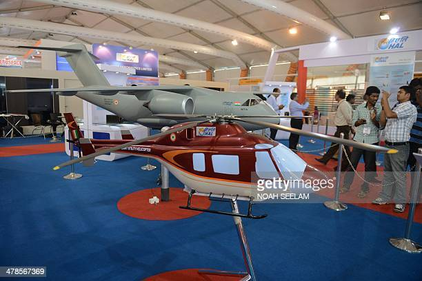 Visitors look at Hindustan Aeronautics Limited Light Utility Helicopters on display at an exhibitors venue at the India Aviation 2014 airshow at...