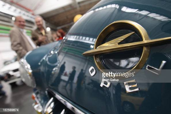 Visitors look at historic Opel cars on display at the Opel Insignia and Astra factory during a celebration marking Opel's 150th anniversary on...