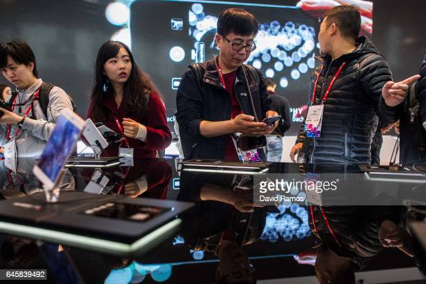 Visitors look at Huawei devices during the Mobile World Congress 2017 on the opening day of the event at the Fira Gran Via Complex on February 27...
