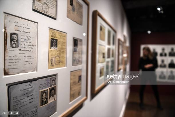 Visitors look at identity cards and photos that are part of the 'Papiers s'il vous plaît' photo exhibition at the photography at the Nicephore Niepce...