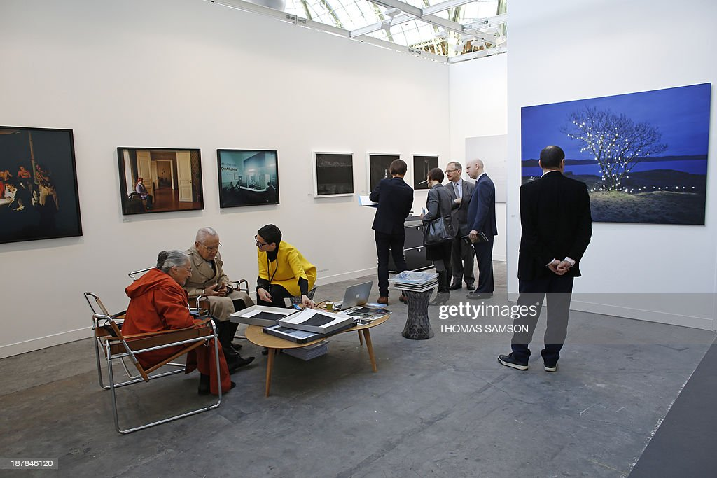 Visitors look at images in an exhibition space during the 17th edition of the Paris Photo photography fair, on November 13, 2013, in Paris. The Paris Photo fair is taking place at the Grand Palais from November 14 to 17.