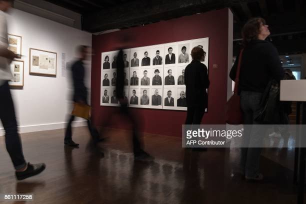 Visitors look at images that are part of the 'Papiers s'il vous plaît' photo exhibition at the photography at the Nicephore Niepce Museum in...
