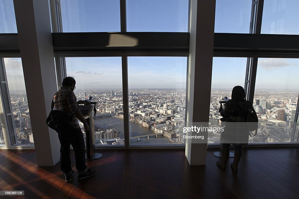 Visitors look at information displays at 'The View From The Shard', a series of viewing galleries looking over the capital, near the top of the Shard tower in London, U.K., on Wednesday, Jan. 9, 2013. The Shard, which stands at 309.6 meters on London's South Bank, is owned by LBQ Ltd., which brings together the State of Qatar (the majority shareholder) and Sellar Property Group Ltd., with non-equity funding by Qatar National Bank. Photographer: Chris Ratcliffe/Bloomberg via Getty Images