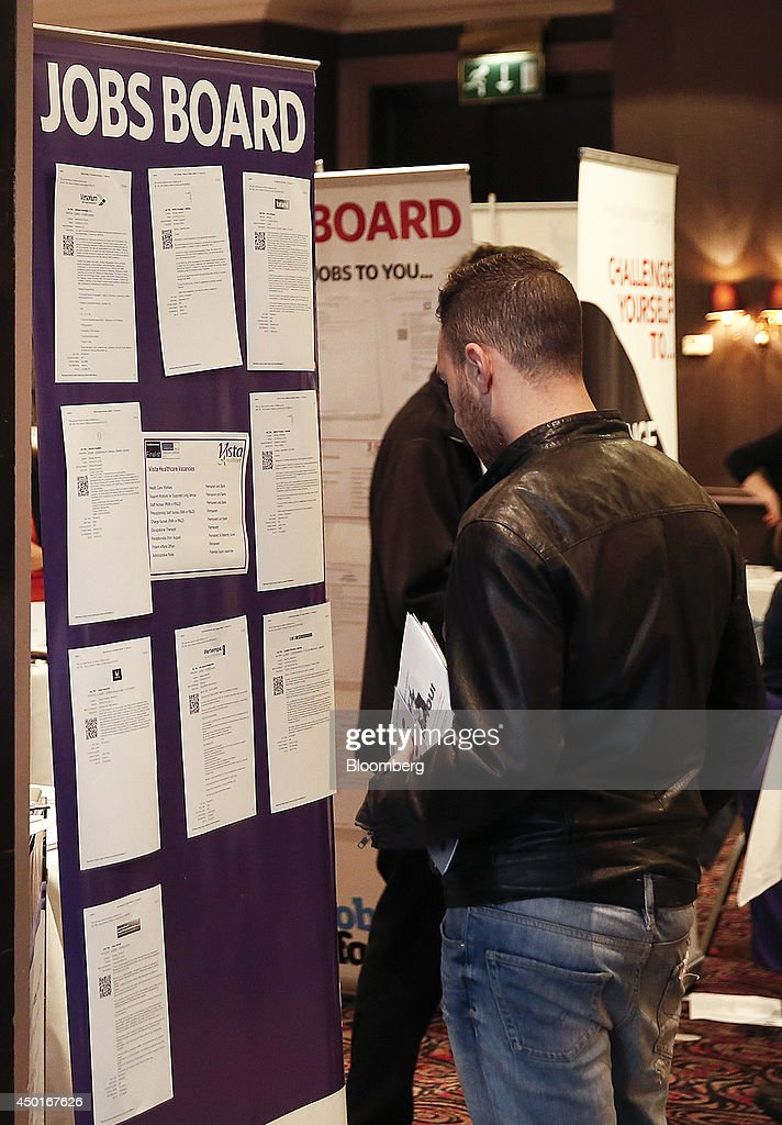 Visitors look at job vacancies and recruitment opportunities displayed during a jobs fair in Reading UK on Friday June 6 2014 Britain's unemployment...