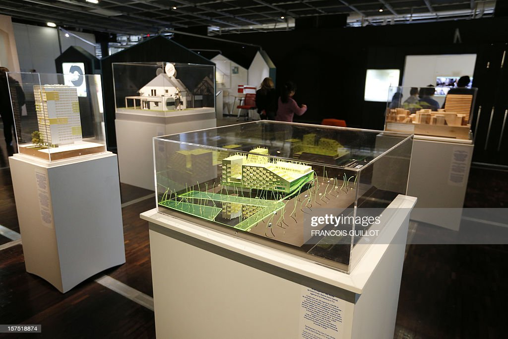 Visitors look at models displayed at the Cite des Sciences et de l'Industrie in Paris on December 4, 2012, as part of the exhibition 'Habiter demain' (Reinventing our homes) focused on the social and human aspects of housing and the new way to build home of the future and renovate houses. The event runs from December 4, 2012 to November 13, 2013. Foreground, a model of 120 social housing and business units in an eco-district in Saint-Ouen, a Paris suburb by X-TU architects office. AFP PHOTO FRANCOIS GUILLOT