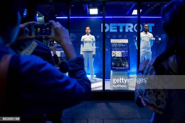 Visitors look at models wearing android costumes from the Detroit Become Human video game during the Tokyo Game Show 2017 at Makuhari Messe in Chiba...