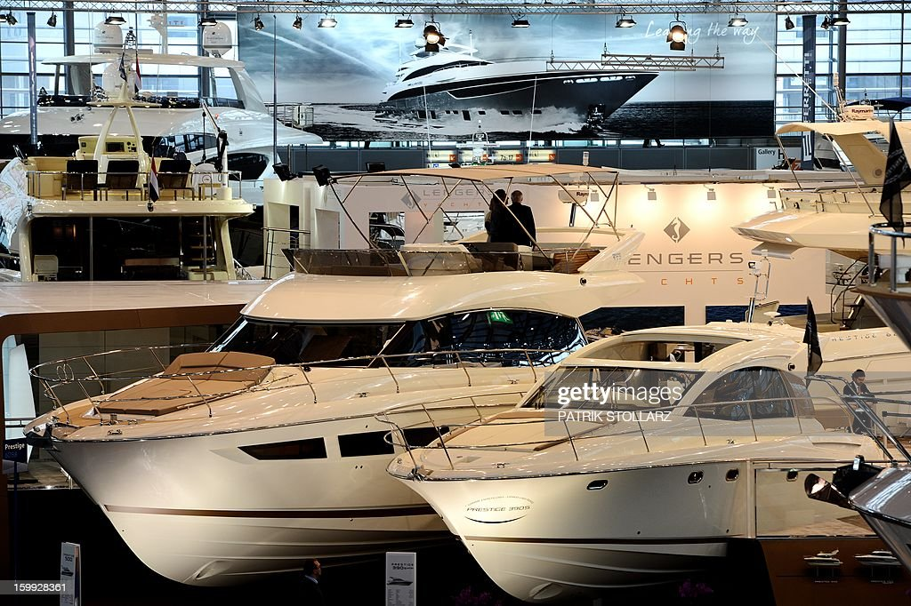 Visitors look at motorboats at the Duesseldorf fairground during the Boot fair International Boat Show on January 23, 2013. The event, running from January 19 to January 27, features all boats, yachts, superyachts, electronics, engines and thousands of accessories from every major marine manufacturer and builder worldwide. AFP PHOTO / PATRIK STOLLARZ