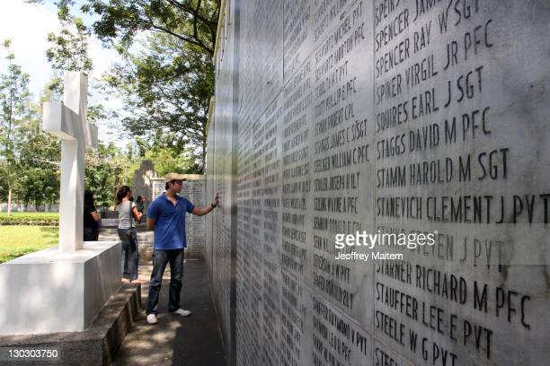 Visitors look at names listed in memory of Filipino and US soldiers who died as prisoners of war from the Bataan Death March during World War II at...