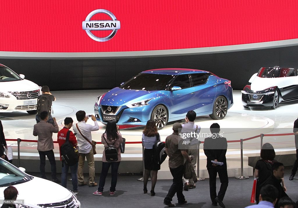 Visitors look at Nissan cars on display at the China International Exhibition Center new venue during the 'Auto China 2014' Beijing International Automotive Exhibition in Beijing on April 20, 2014. Leading automakers are gathering in Beijing for the kickoff of China's biggest car show, but lackluster growth and environmental restrictions in the world's largest car market have thrown uncertainty into the mix. More than 1,100 vehicles are being showcased at the auto show, which opens to the public on April 21. CHINA