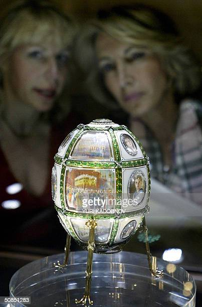 Visitors look at one of the nine Faberge imperial eggs displayed at an exhibition in the Kremlin in Moscow 18 May 2004 A stunning collection of nine...
