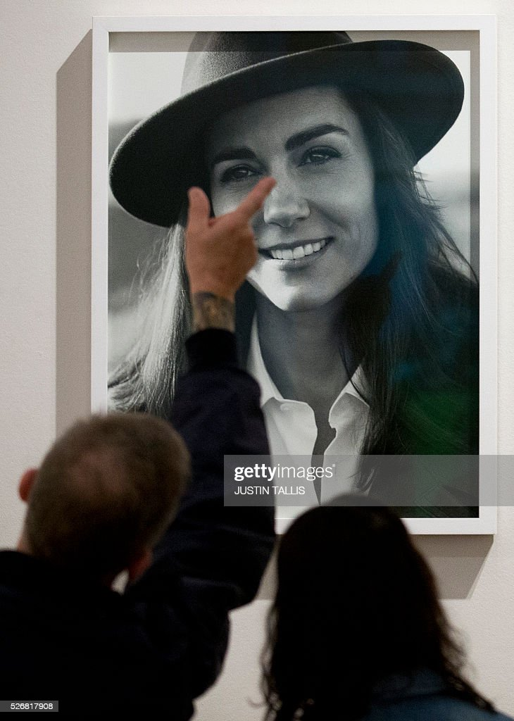 Visitors look at one of two new portraits of Catherine, Duchess of Cambridge, taken in the Norfolk Countryside by British photographer Josh Olins, at the Vogue 100: A Century of Style exhibition at the National Portrait Gallery in London on May 1, 2016. / AFP / JUSTIN