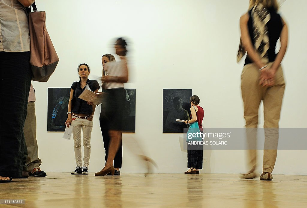 Visitors look at paintings by Romanian artist Victor Man on June 25, 2013 during an exhibition at the Villa Medici, the headquarters of the French Academy in Rome.
