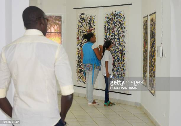 Visitors look at paintings by Tuareg poet and painter Hawad on April 6 in Niamey The BoubouHama National Museum in Niamey and the FrancoNigerien...