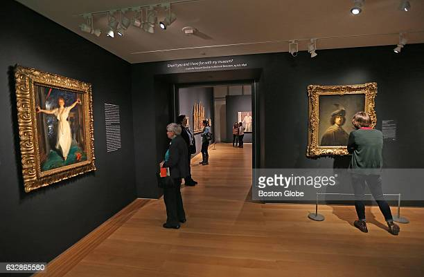 Visitors look at paintings in the Isabella Stewart Gardner Museum's 'Off The Walls' exhibition in which some of the museum's most precious paintings...