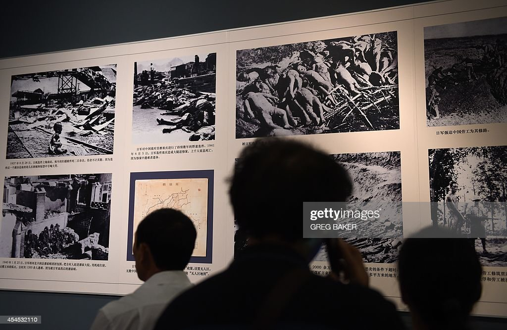 Visitors look at photos of the aftermath of Japanese attacks on Chinese cities at an exhibition about World War II in Beijing on September 3, 2014. Chinese President Xi Jinping and all six other members of the Politburo Standing Committee, the country's most powerful body, made a rare public appearance Sept 3 to commemorate 69 years since Japan's surrender at the end of World War II. AFP PHOTO/Greg BAKER -- RESTRICTED