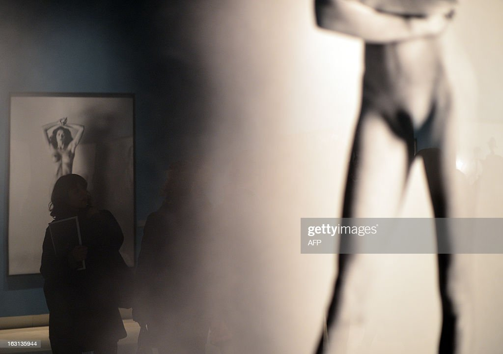 Visitors look at pictures by German-Australian photographer Helmut Newton during a press preview of the 'White women / Sleepless nights / Big nudes' exhibition at the Palazzo delle Esposizioni on March 5, 2013 in Rome. The exhibition will run from March 6 to July 21, 2013. AFP PHOTO / GABRIEL BOUYS RESTRICTED TO EDITORIAL USE, MANDATORY CREDIT OF THE ARTIST, TO ILLUSTRATE THE EVENT AS SPECIFIED IN THE CAPTION