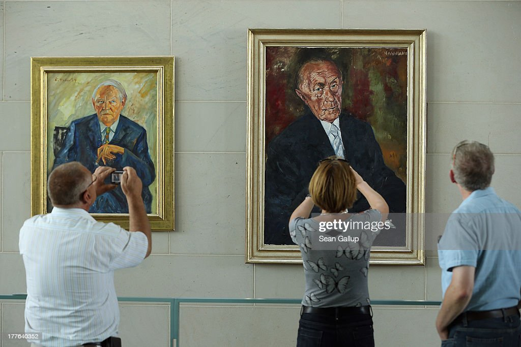 Visitors look at portraits of past German chancellors Ludwig Erhard (L) and Konrad Adenauer during the annual open-house day at the Chancellery on August 25, 2013 in Berlin, Germany. Approximately 150,000 visitors took advantage of the annual event held at the Chancellery and German government ministries to get an inside glimpse.