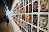 Visitors look at portraits of US soldiers killed in Iraq on the first day of the exhibition 'To Never Forget The Faces of the Fallen' in the Shaffer...