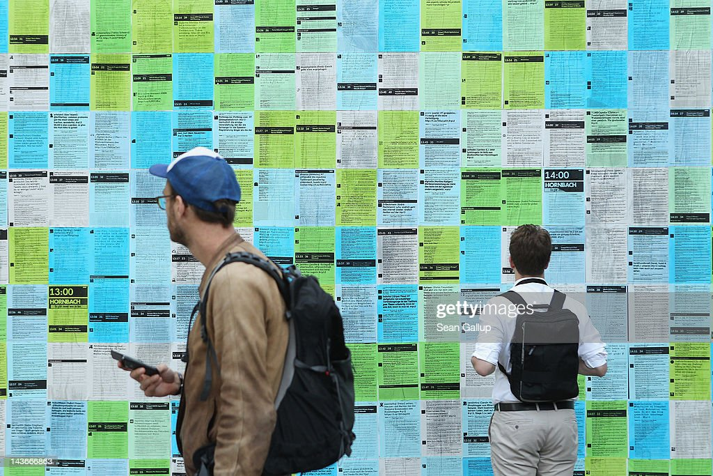 Visitors look at printouts of the day's tweets during the 2012 re.publica conferences on May 2, 2012 in Berlin, Germany. The re:publica conferences bring bloggers, hackers and activists together for conferences whose themes involve digital society.