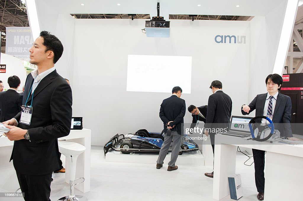 Visitors look at products displayed at the AMS AG booth at Automotive World 2013 in Tokyo, Japan, on Friday, Jan. 18, 2013. The Automotive World 2013 trade show ends today. Photographer: Noriko Hayashi/Bloomberg via Getty Images