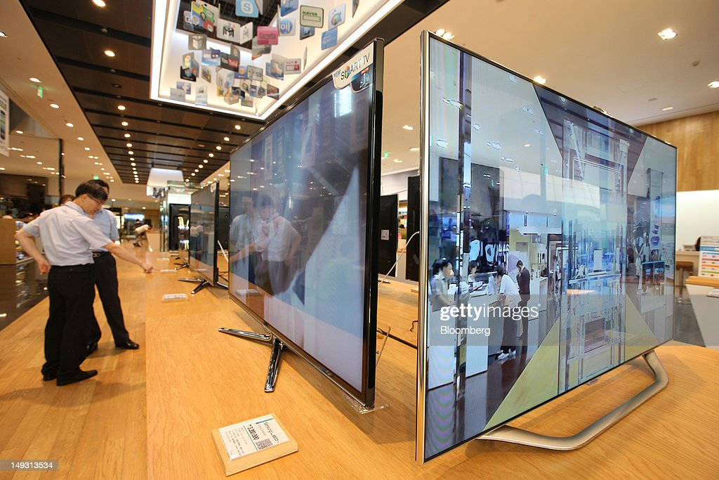 Visitors look at Samsung Electronics Co. smart televisions at the company's flagship store in Seoul, South Korea, on Thursday, July 26, 2012. Samsung, the world's largest maker of TVs and mobile phones, reported second-quarter profit that missed analysts' estimates after chip prices weakened and smartphone output failed to keep up with demand. Photographer: SeongJoon Cho/Bloomberg via Getty Images