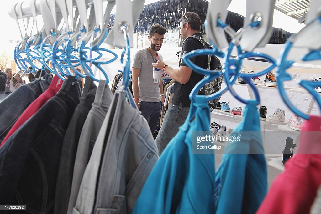 Visitors look at shoes and denim at the adidas Originals Spring/Summer 13 collection at the Bread and Butter 2012 fashion trade fair on July 4, 2012 in Berlin, Germany.
