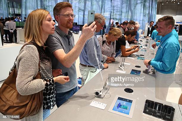 Visitors look at smart phones at the Samsung stand at the 2015 IFA consumer electronics and appliances trade fair on September 4 2015 in Berlin...