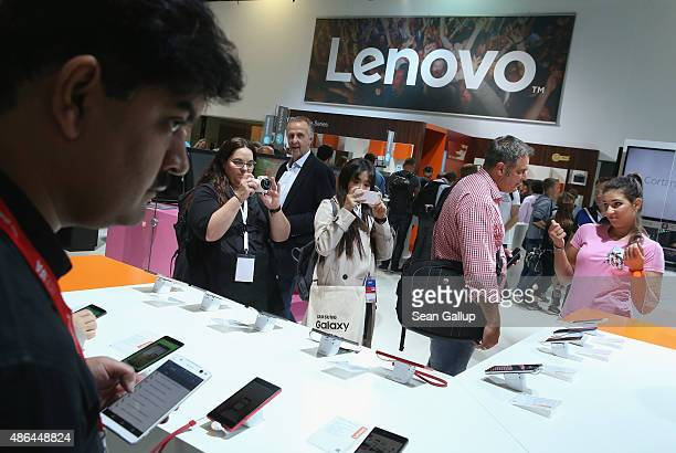 Visitors look at smartphones at the Lenovo stand at the 2015 IFA consumer electronics and appliances trade fair on September 4 2015 in Berlin Germany...