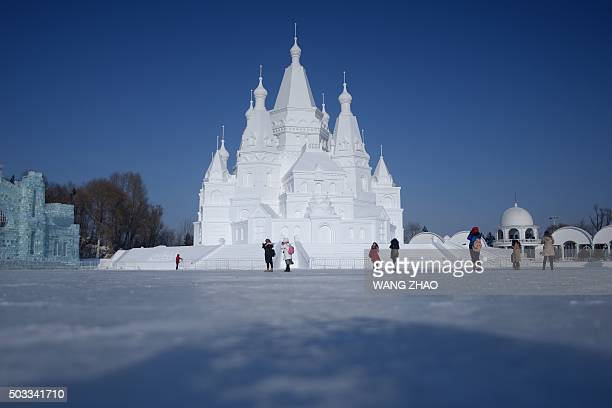 Visitors look at snow sculptures before the opening ceremony of the Harbin International Ice and Snow Festival in Harbin northeast China's...