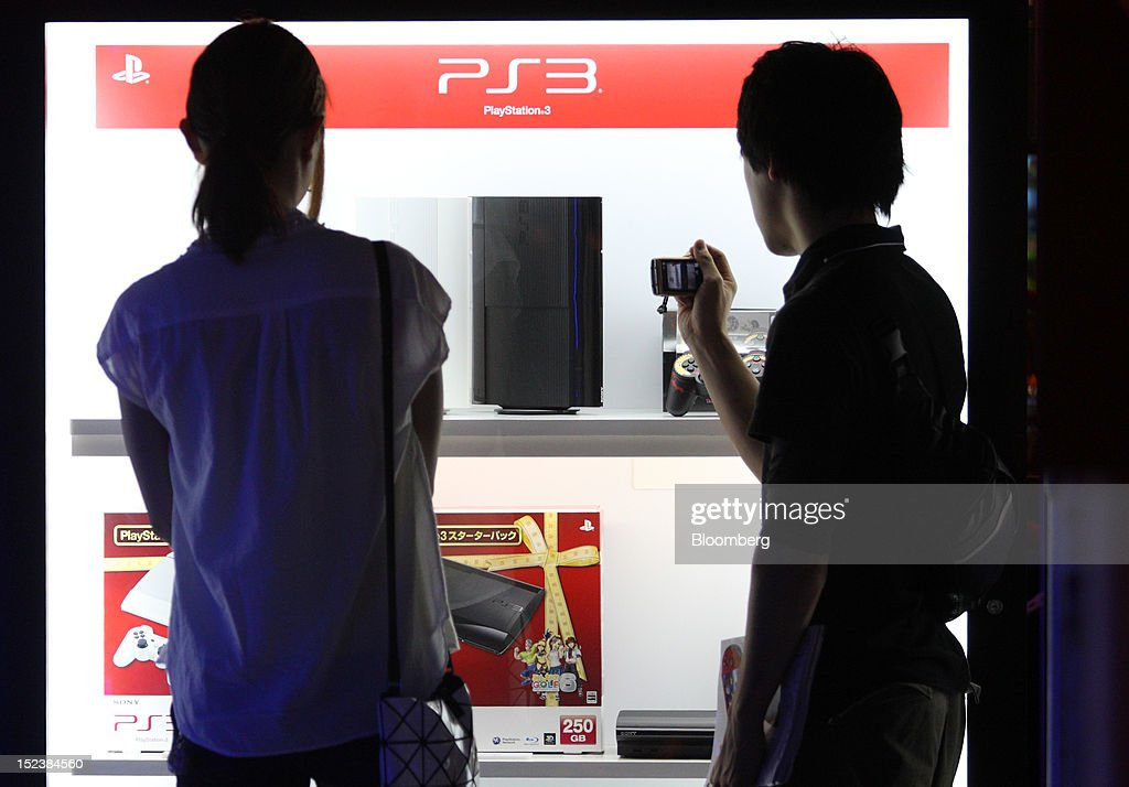 Visitors look at Sony Computer Entertainment Inc. PlayStation 3 game consoles displayed at the Tokyo Game Show 2012 at Makuhari Messe in Chiba, Japan, on Thursday, Sept. 20, 2012. The show will be held through Sept. 23. Photographer: Tomohiro Ohsumi/Bloomberg via Getty Images