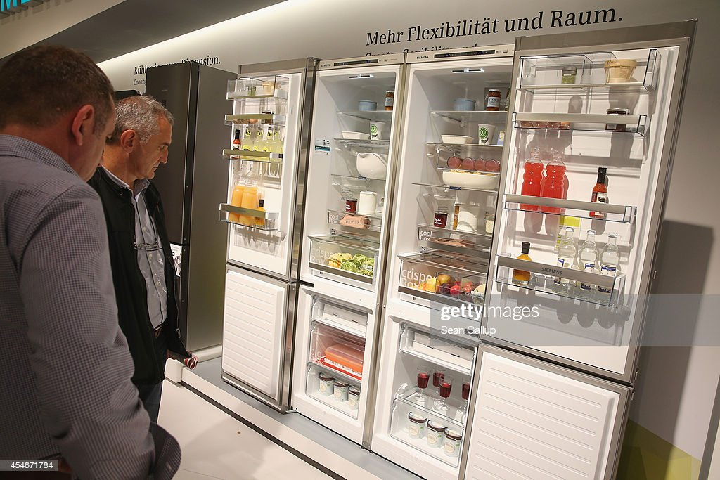 Visitors look at spacesaving refrigerators at the Siemens stand at the 2014 IFA home electronics and appliances trade fair on September 5 2014 in...