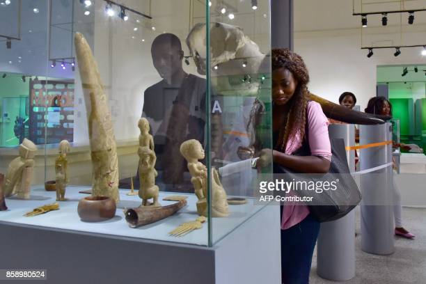 Visitors look at statues exhibited at the Civilisation Museum of Abidjan on September 29 2017 during the first exhibition called 'Renaissance'...