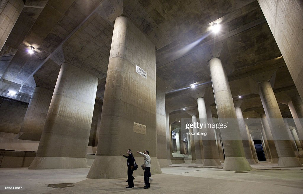 Visitors look at stone pillars in the surge tank area of the Metropolitan Area Outer Underground Discharge Channel in Kasukabe City, Saitama Prefecture, Japan, on Wednesday, Nov. 21, 2012. The facility called 'Underground Temple' was constructed to protect the capital Tokyo against flooding and is one of the largest underground water diversion facilities in the world. Photographer: Tomohiro Ohsumi/Bloomberg via Getty Images