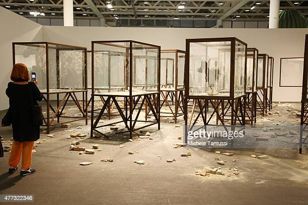 Visitors look at the artwork of Kader Attia Arab Spring 2014 during the press preview day at ART Basel on June 16 2015 in Basel Switzerland