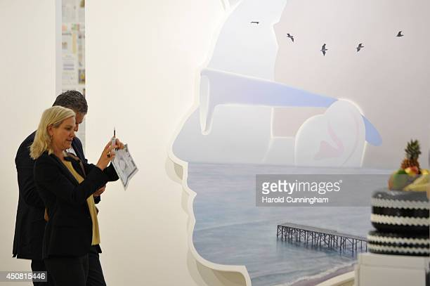 Visitors look at the artwork 'Self Portrait ' by Alex Israel in the gallery section of Art Basel on June 18 2014 in Basel Switzerland Art Basel one...