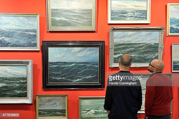 Visitors look at the artwork 'Untitled' by HansPeter Feldmann during Art Basel on June 16 2015 in Basel Switzerland Art Basel one of the most...