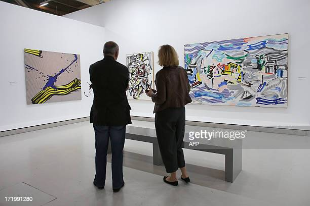 Visitors look at the artworks 'Brushstroke with spatter' 'Woman' and 'Fishing Village' by late US artist Roy Lichtenstein on June 30 2013 at the...