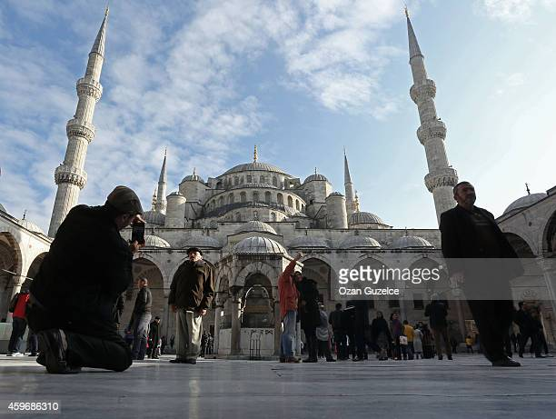 Visitors look at the Blue Mosque before Pope Francis visit in central Istanbul on November 28 2014 Pope Francis arrived in Turkey on Friday at a...