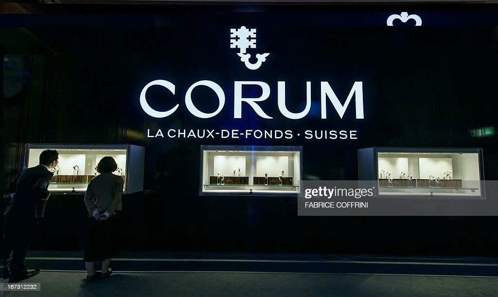 Visitors look at the booth of Swiss watchmaker Corum during the press preview day of watch fair Baselworld on April 24, 2013 in Basel. Swiss watches Corum were bought by Chinese group China Haidian, according to a statement released by the Swiss company. The amount of the transaction, announced on the eve of the opening of the largest international watch fair Baselworld, was not disclosed. This is the first acquisition in the Swiss haute horlogerie by a Chinese group. AFP PHOTO / FABRICE COFFRINI