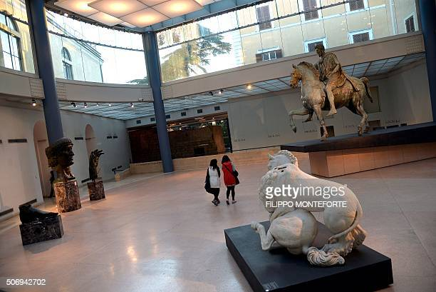 Visitors look at the Constantine bronze head and the original equestrian bronze statue of Marco Aurelio on display at Rome's Capitoline Museum on...