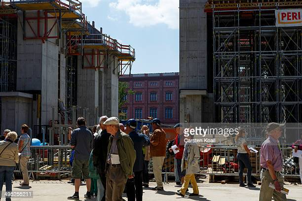 Visitors look at the construction site of the construction work of the Berlin City Palace in Berlin's city center during a public day of the visit on...