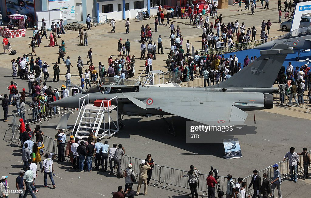 Visitors look at the Dassault Rafale fighter aircraft on the fifth and final day of Aero India 2013 at Yelahanka Air Force station in Bangalore on February 10, 2013. India, the world's leading importer of weaponry, opened one of Asia's biggest aviation trade shows February 6 with Western suppliers eyeing lucrative deals and a Chinese delegation attending for the first time.