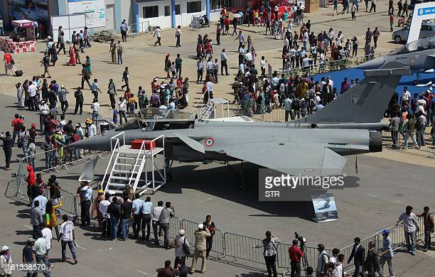 Visitors look at the Dassault Rafale fighter aircraft on the fifth and final day of Aero India 2013 at Yelahanka Air Force station in Bangalore on...