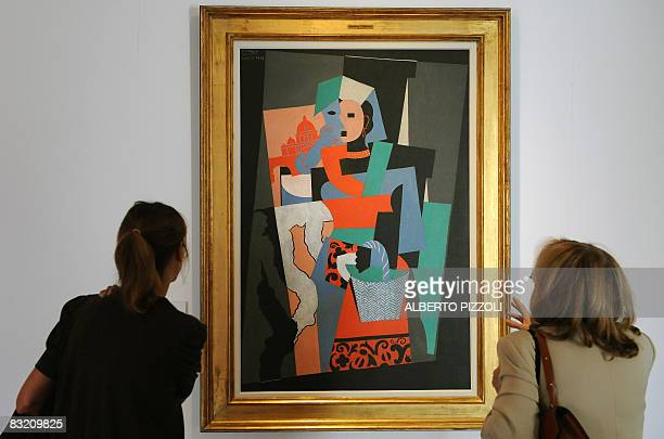 Visitors look at 'The Italian woman' by cubist master Pablo Picasso during the 'Picasso 19171937 The Harlequin of Art' exhibition on October 10 2008...