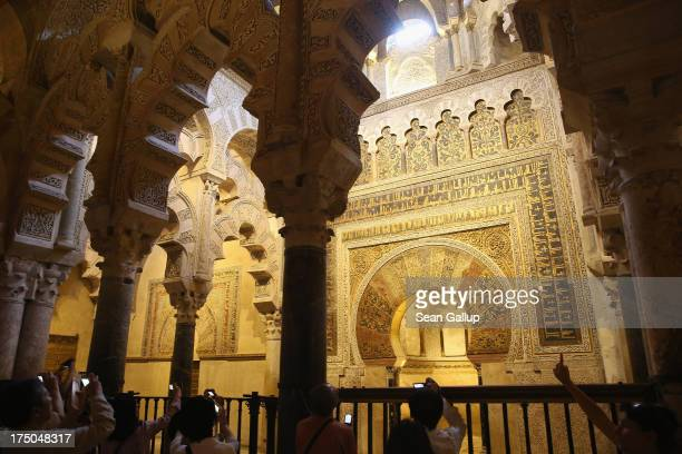 Visitors look at the mihrab in the MosqueCathedral of Cordoba on July 23 2013 in Cordoba Spain Southern Spain is among the most popular tourist...