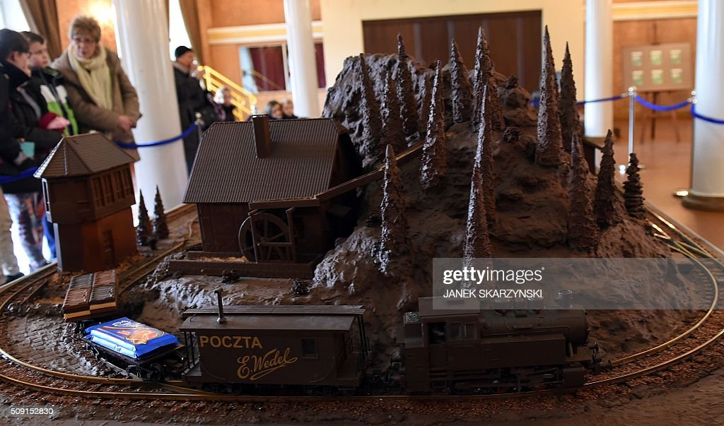 Visitors look at the mock-up of a train driving through a landscape made out of chocolate at the Warsaw Railway Museum on February 9, 2016 in Warsaw. Five hundred kilograms of chocolate were used to make the model. Everything is edible, besides the tracks and the engine. / AFP / JANEK SKARZYNSKI