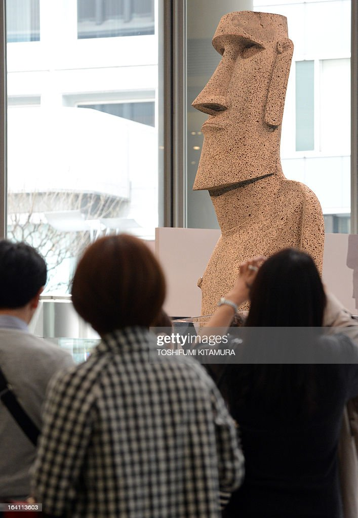 Visitors look at the new 'Moai' statue (top R), modelled on the mysterious carvings at Easter Island, presented to the tsunami-devastated town of Minamisanriku during its preview in Tokyo on March 20, 2013. The giant present crossed the ocean from Chile as the town's original was destroyed in the March 11 quake-sparked tsunami disaster in 2011. AFP PHOTO / TOSHIFUMI KITAMURA