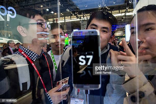 Visitors look at the new Samsung Galaxy S7 on the opening day of the World Mobile Congress at the Fira Gran Via Complex on February 22 2016 in...